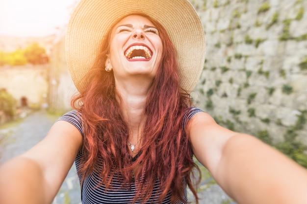 Gelukkige vrouwelijke toerist naast muur Gratis Foto