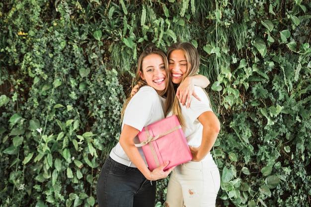 Gelukkige vrouwelijke vrienden met roze giftdoos die zich voor groene bladeren bevinden Gratis Foto