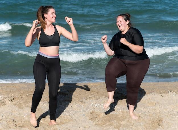 Gelukkige vrouwen die samen volledig schot trainen Gratis Foto