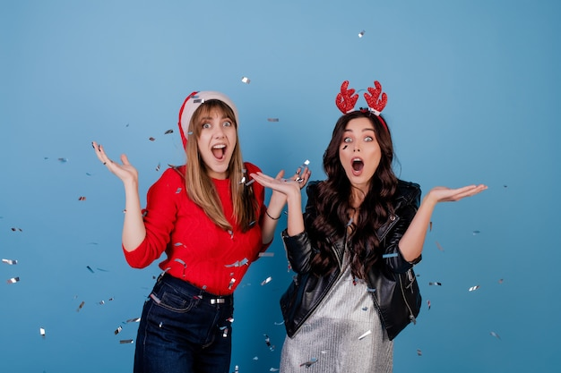 Gelukkige vrouwen met zilveren confettien in de lucht die kerstmishoed dragen die over blauw wordt geïsoleerd Premium Foto