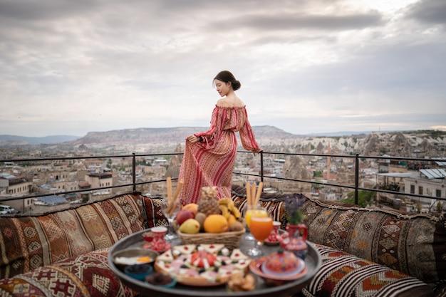 Gelukkige vrouwen op dak van holhuis het genieten van van goreme-stadspanorama, cappadocia turkije. Premium Foto
