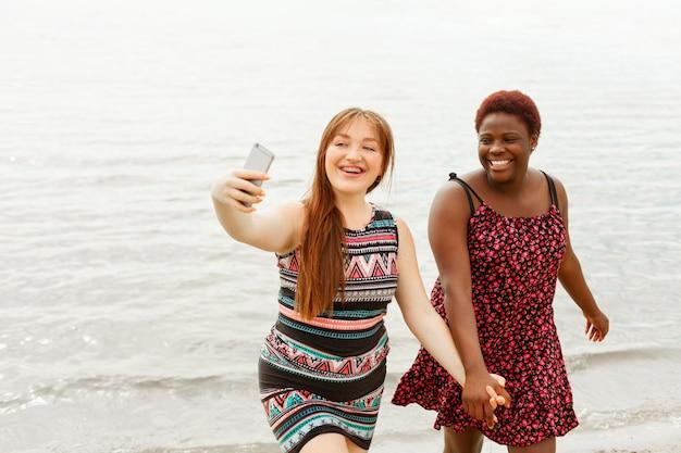 Gelukkige vrouwen op het strand hand in hand en selfie te nemen Gratis Foto