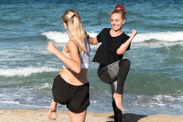 Gelukkige vrouwen trainen samen op het strand Gratis Foto