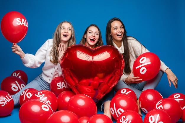 Gelukkige vrouwenvrienden die met rode hartvormige ballon stellen Gratis Foto
