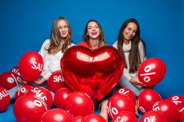 Gelukkige vrouwenvrienden poseren met rode hartvormige ballon en luchtballen met procent en verkoop belettering op blauwe achtergrond Premium Foto