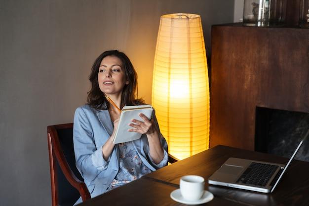 Gelukkige vrouwenzitting die binnen nota's schrijven. Gratis Foto