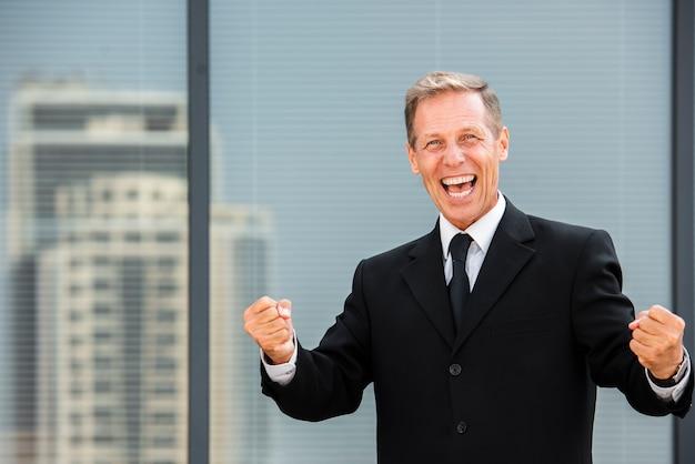 Gelukkige zakenman die camera bekijkt die dichtbij bouwt Gratis Foto