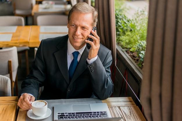 Gelukkige zakenman die op mobiele telefoon met kop van koffie en laptop op lijst spreken Gratis Foto