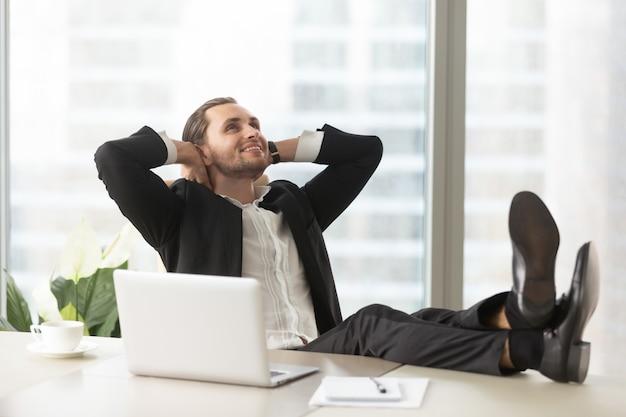 Gelukkige zakenman die over goede perspectieven denkt Gratis Foto