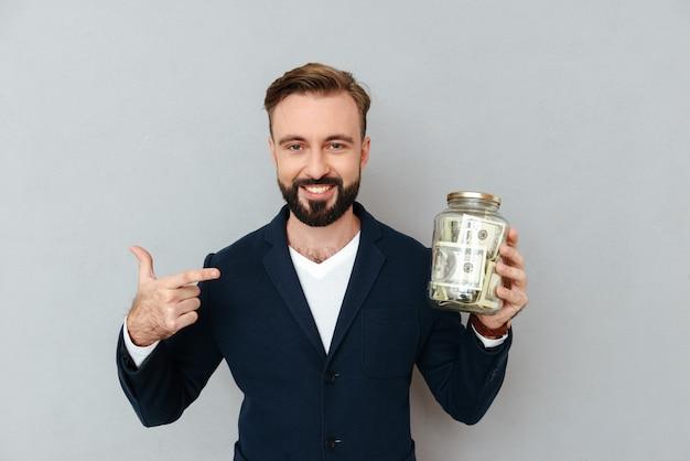 Gelukkige zekere mens die op doos met geïsoleerd geld richt Gratis Foto