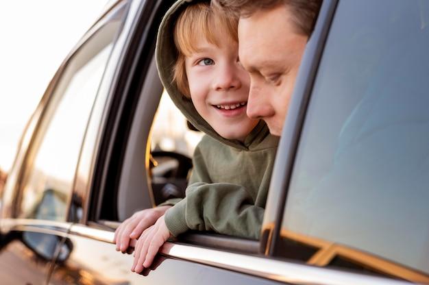 Gelukkige zoon in de auto met vader op een roadtrip Gratis Foto