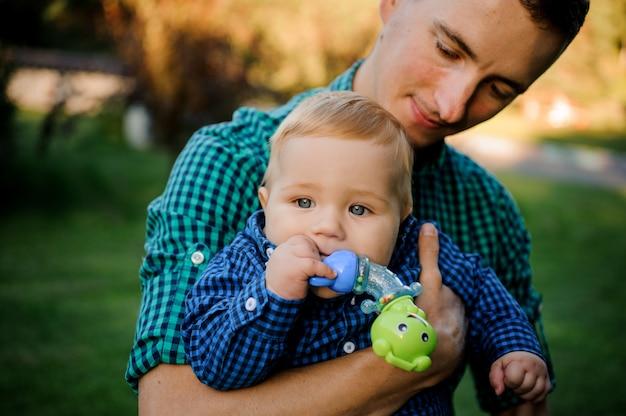 Gelukkige zorgzame vader die op handen een babyjongen met een fopspeen houdt Premium Foto