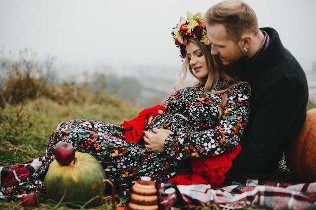 Gelukkige zwangere paar geniet van hun tijd samen liggend op de wet Gratis Foto