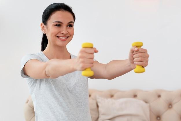 Gelukkige zwangere vrouw die gele gewichten gebruikt Gratis Foto