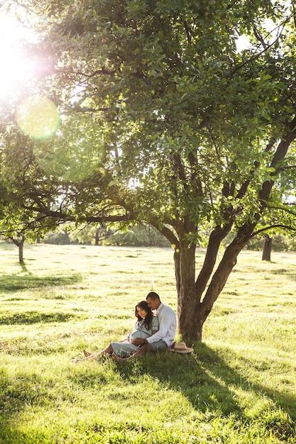 Gelukkige zwangere vrouw met haar echtgenoot bij zonsondergang Premium Foto