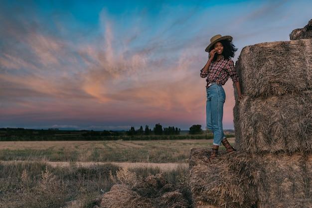 Gelukkige zwarte jonge vrouw die zich op een stapel van hooi bevindt Premium Foto
