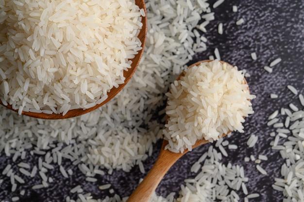 Gemalen rijst in een kom en een houten lepel op de zwarte cementvloer. Gratis Foto
