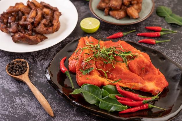 Gemarineerd varkensvlees gebruikt in de keuken, compleet met chili pepers kaffir limoenblaadjes in een zwarte plaat Gratis Foto