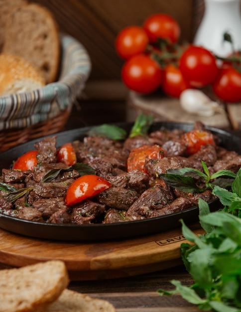 Gemarineerde plakjes rundvlees gegarneerd met dragon en tomaat Gratis Foto