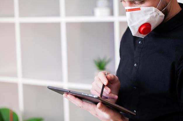 Gemaskerde mens die aan tablet op bedrijfkantoor werken Premium Foto