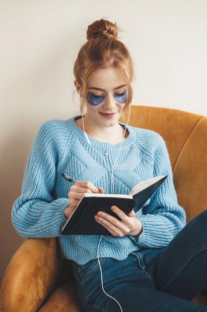 Gember vrouw met sproeten schrijven iets in een boek draagt hydrogel eye patches zittend in een stoel Premium Foto