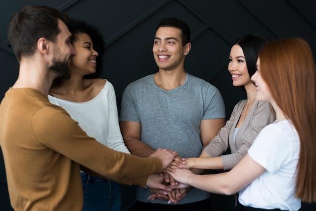 Gemeenschap van jongeren hand in hand samen Gratis Foto