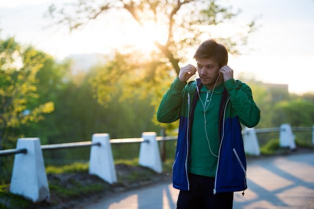 Gemeenschappelijke jonge eenzame mens die in de stad lopen die aan muziek met in-ear hoofdtelefoons luisteren bij zonsondergang. zacht warm licht. Premium Foto