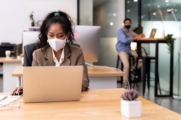 Gemengd ras van afrikaanse zwarte en aziatische zakenvrouw dragen gezichtsmasker werken in nieuw normaal kantoor. Premium Foto