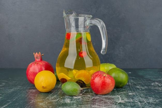 Gemengd vers fruit en een glas sap op marmeren tafel. Gratis Foto