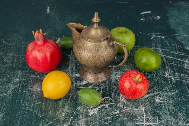 Gemengd vers fruit en klassieke theepot op marmeren tafel. Gratis Foto