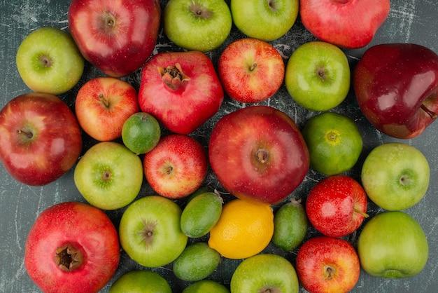 Gemengd vers fruit verspreid over marmeren oppervlak. Gratis Foto