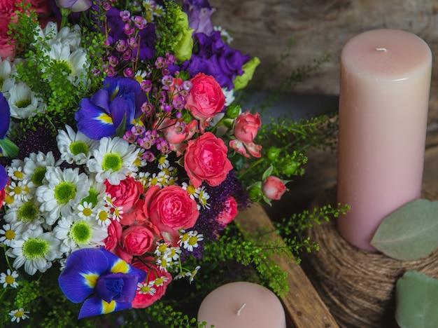 Gemengde bloemen en roze aromakaarsen. Gratis Foto