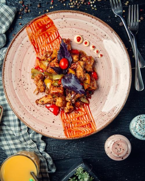 Gemengde gebakken groenten en vlees gegarneerd met basilicum Gratis Foto