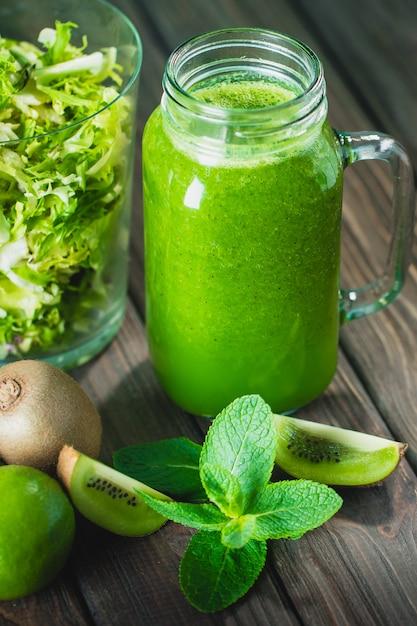 Gemengde groene smoothie met ingrediënten op houten tafel Premium Foto