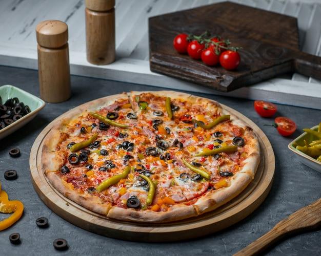Gemengde ingrediëntpizza met chilipepers en olijfrolletjes. Gratis Foto