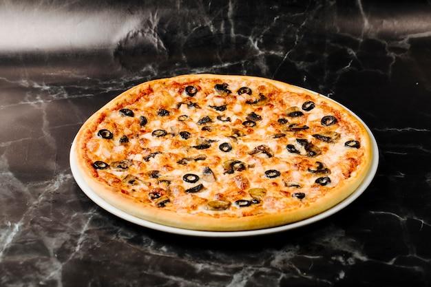 Gemengde ingrediëntpizza met zwarte olijfbroodjes. Gratis Foto