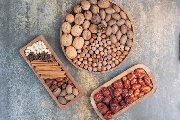 Gemengde noten met pijpjes kaneel en gedroogd fruit op houten plaat. hoge kwaliteit foto Gratis Foto