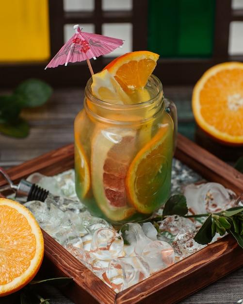 Gemengde sinaasappel en grapefruitsapcocktail in een glazen pot. Gratis Foto
