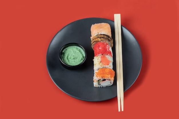 Gemengde sushi rolt in een zwarte plaat met sauzen. Gratis Foto
