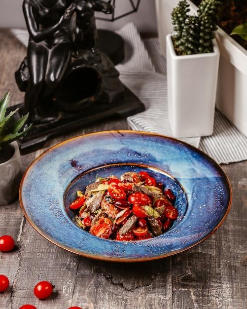 Gemengde tomaten en vlees in blauwe plaat Gratis Foto
