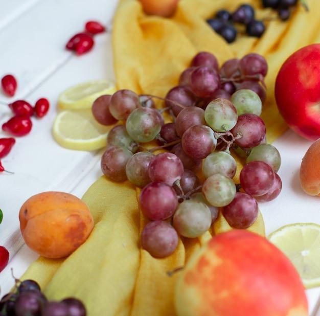 Gemengde vruchten op een geel lint op een witte tafel. Gratis Foto