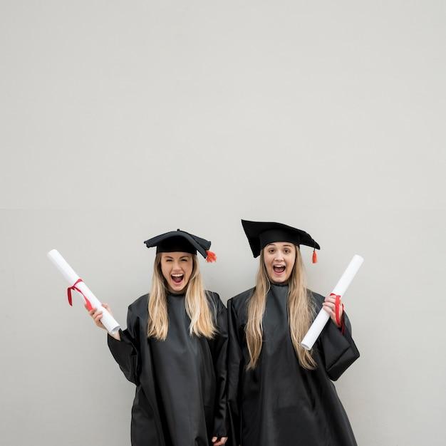 Gemiddeld geschotene gelukkige meisjes die een diploma behalen Gratis Foto