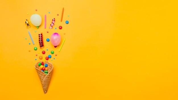 Gems; hagelslag; streamers; kaarsen en ballon over de wafelkegel op gele achtergrond Premium Foto