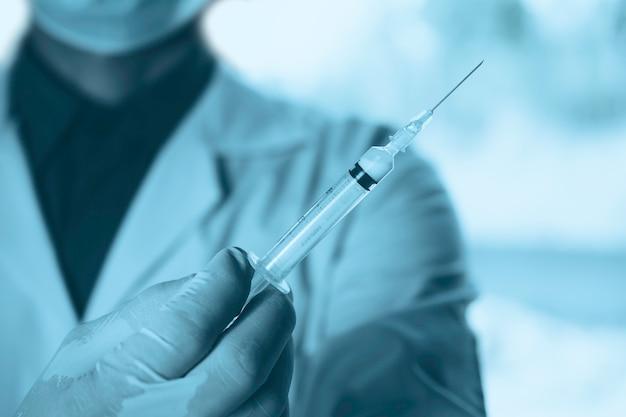 Geneeskunde arts met een spuit in de hand. gezondheidszorg en medisch concept. Premium Foto
