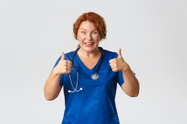 Geneeskunde, gezondheidszorg en coronavirus-concept. vrolijke roodharige arts van middelbare leeftijd raadt kliniekaanbieding of covid-19-testkorting aan, duimen omhoog en glimlachend, keuze goed, grijze achtergrond. Premium Foto