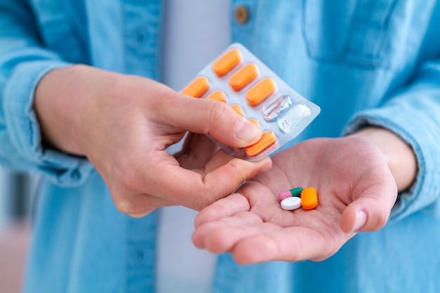 Geneeskundevrouw die pillen en vitaminen thuis voor wellness nemen. gezondheidszorg en behandelingsziekten. Premium Foto