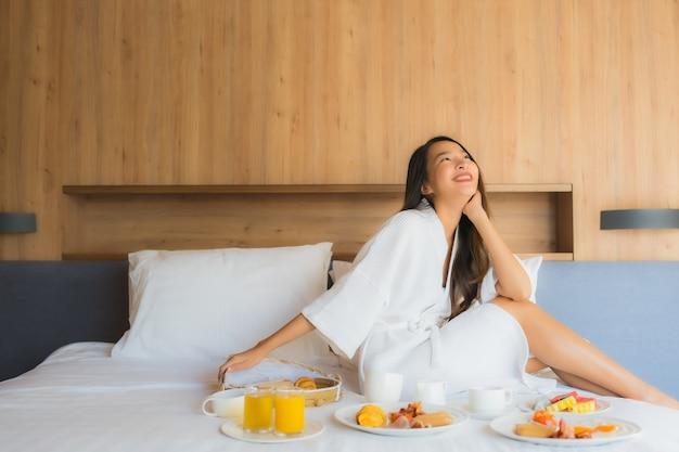 Geniet de portret mooie jonge aziatische gelukkige vrouw van met ontbijt op bed in slaapkamer Gratis Foto