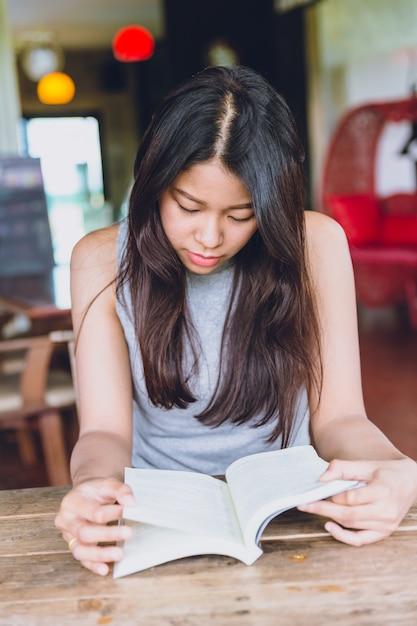 Geniet van ontspannen tijden met het lezen van boek, aziatische vrouwen thaise tiener serieus aandacht te lezen pocketbook in coffeeshop Premium Foto