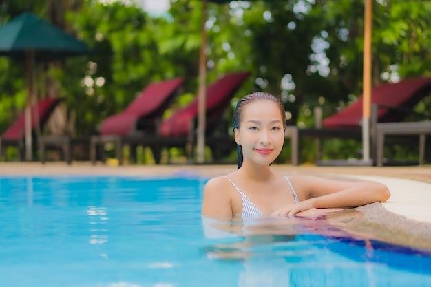 Geniet van ontspannende glimlachvrije tijd van de portret mooie jonge aziatische vrouw rond openluchtzwembad in hotel Gratis Foto