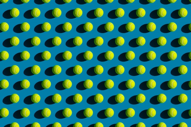 Geometrisch patroon van tennisballen met sterke schaduwen op een blauw Premium Foto